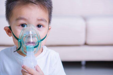 Closeup asiatisches Gesicht kleine Kinder Junge krank er mit Dampfinhalator Vernebler Maske Inhalation selbst, medizinische Versorgung Standard-Bild