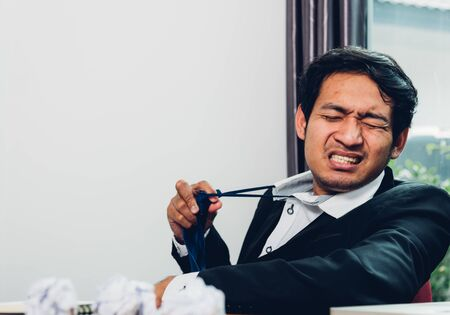 Young asian business man manager frustrated he has tired after work long time