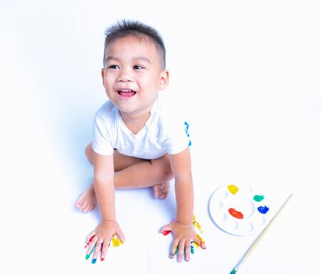 Happy asian child playful he is playing water color or finger print on white paper, Baby 2-3 years 版權商用圖片