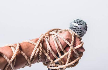 Main tenant le microphone et ont encordé le poing sur fond blanc, concept de la journée des droits de l'homme