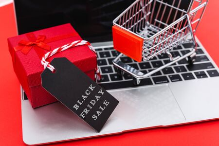 Internet online shopping marketing, top view of workspace with Black Friday text black tag, gift box and cart shopping on laptop computer on red background and have copy space for use