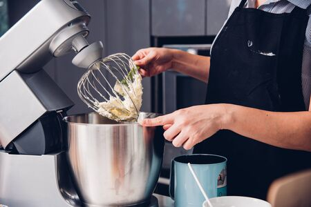 Woman making mixer bakery cake machine at the home