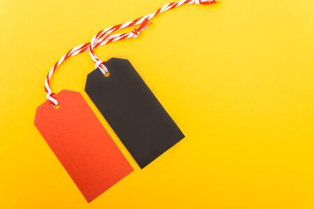 Red tag label and Black tag label on yellow background, blank copy space for you work Stock fotó