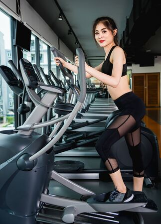 Young woman lifestyle using equipment machine elliptical for training cardio workout at fitness gym