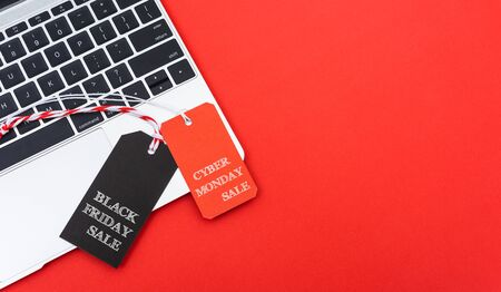 Internet online shopping marketing, top view of workspace with Black Friday text black tag and Cyber Monday text red tag near laptop computer on red background