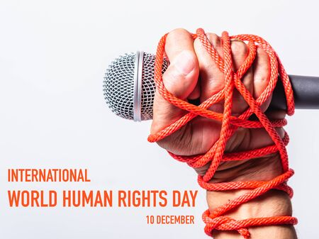 Hand holding microphone and have roped on fist hand with 10 december international HUMAN RIGHTS DAY text on white background, Human rights day concept