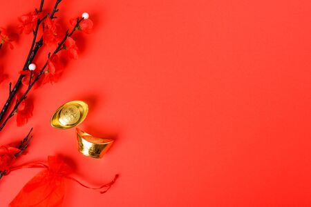 Chinese New Year, flat lay top view, gold bar and Chinese Flower on red background with copy space for your text