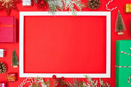 Christmas composition decorations, fir tree branches with Photo square frame on red background. Merry Christmas concept. Copy space for text