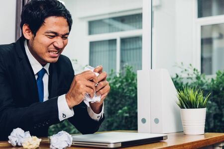 Business man frustrated he has angry paper crumpled on desk table office