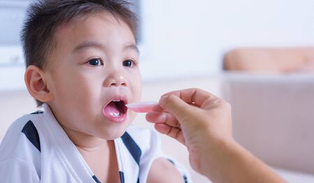 Asian children boy sick he take medicine by spoon ,medical care