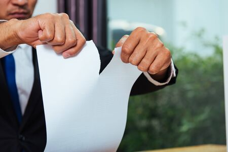 Business man angry tearing paper document on desk office