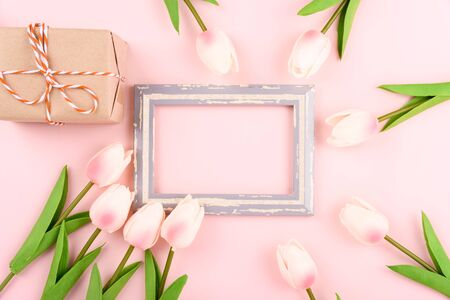 Happy Womens Day, Mothers Day concept. top view flat lay photo frame, gift box and Tulip flower on pink background, copy space for your text