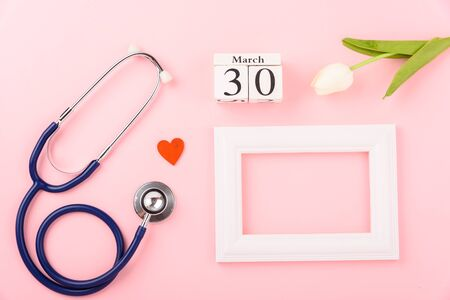 Doctor's Day concept, flat lay top view, equipment medical red heart stethoscope and photo frame on pink background, care patient in hospital with copy space for text Stok Fotoğraf