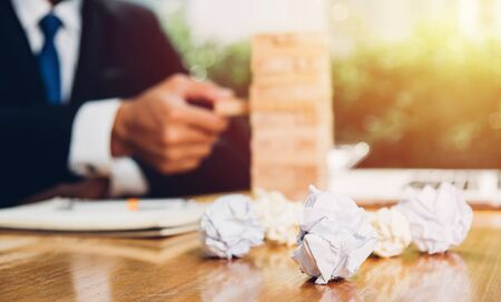 Business man risk he pulling block wood tower and have crumpled paper on desk table