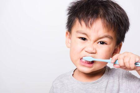 Asiatisches Gesicht der Nahaufnahme, kleine Kinderjungenhand hält Zahnbürste, die er selbst die Zähne auf weißem Hintergrund mit Kopienraum putzt, medizinische Versorgung des Gesundheitswesens