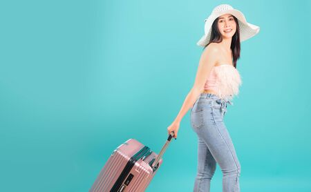Portrait asian beautiful woman with hat her drag luggage or travel bag to travel weekends on blue background, with copy space for text