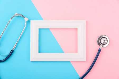 Doctor's Day concept, flat lay top view, stethoscope with photo frame on pink blue background, diagnosis of heart disease with copy space for text