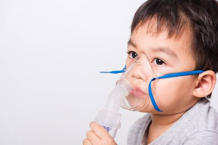 Closeup Asian face, Little children boy sick he using steam inhaler nebulizer mask inhalation oneself on white background, health medical care