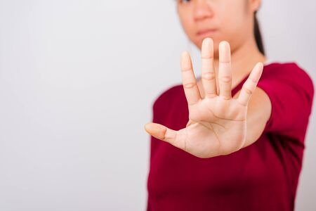 Asian beautiful woman itching her outstretched hand showing stop gesture front face, focus on hand on white background with copy space