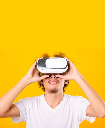 Asian handsome man with curly hair he using virtual reality headset or VR glass isolate on yellow background 写真素材