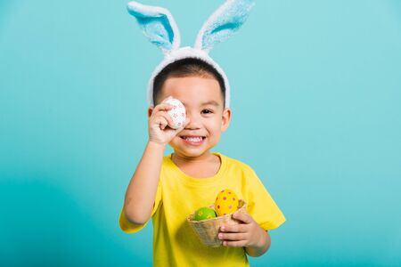 Asian cute little child boy smile beaming wearing bunny ears and a yellow T-shirt, standing to holds colored easter eggs instead of eyes on blue background with copy space for text
