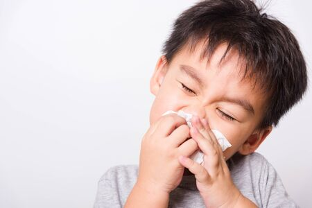 Closeup Asian face, Little children boy cleaning nose with tissue on white background with copy space, health medical care
