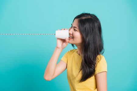 Portrait happy Asian beautiful young woman smile white teeth standing wear yellow t-shirt, She holding paper can telephone for talking, studio shot on blue background with copy space for text