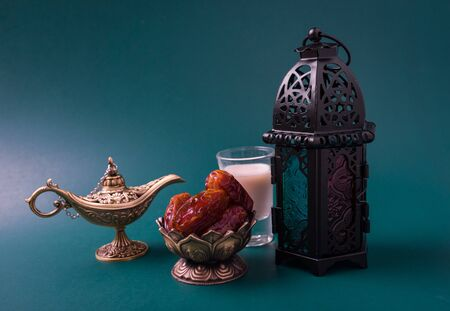 Ramadan Kareem fasting Food Concept, Bronze plate dates, milk, and lantern Aladdin lamp decoration, eid Arabian Muslim religious festival on a dark green background with copy space for text Stock Photo