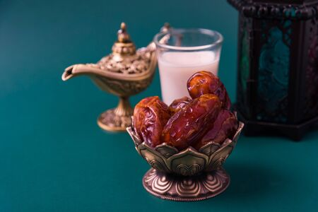 Ramadan Kareem fasting Food Concept, Bronze plate dates, milk, and lantern Aladdin lamp decoration, eid Arabian Muslim religious festival on a dark green background with copy space for text Archivio Fotografico