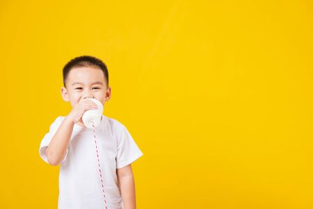 Portrait happy Asian cute little children boy smile standing so happy wearing white T-shirt playing paper can telephone, studio shot on yellow background with copy space