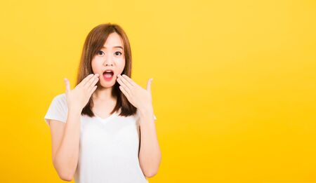 Asian happy portrait beautiful cute young woman teen standing amazed, shocked afraid wide open mouth eyes gesturing palms looking to camera isolated, studio shot on yellow background with copy space