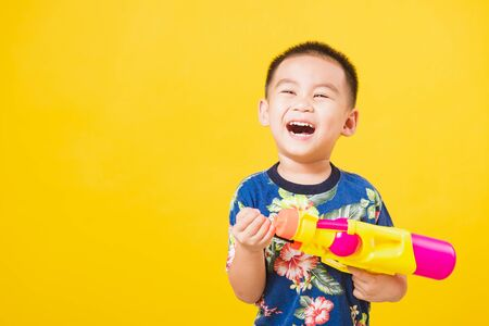Portrait happy Asian cute little children boy smile standing so happy wearing flower shirt in Songkran festival day holding water gun, studio shot on yellow background with copy space Stock Photo