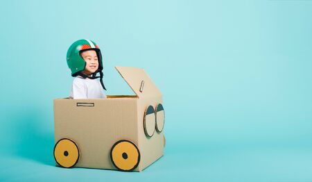 Happy Asian children boy with Helmet smile in driving play car creative by a cardboard box imagination, summer holiday travel concept, studio shot on blue background with copy space for text