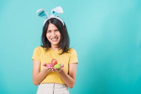 Portrait Asian beautiful happy young woman smile white teeth wear yellow t-shirt standing with bunny ears and holding Easter eggs looking to camera, on a blue background with copy space 版權商用圖片