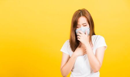 Asian happy portrait beautiful cute young woman teen standing wear t-shirt cough in mask protection from virus epidemic or air pollution isolated, studio shot on yellow background with copy space Standard-Bild