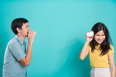 Asian happy young couple beautiful handsome smile and talking together with paper can telephone in a studio shot on blue background with copy space for text