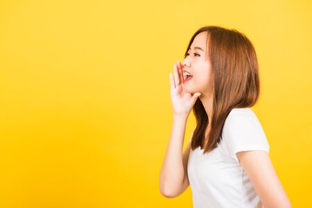 Asian happy portrait beautiful cute young woman teen standing wear t-shirt hand on mouth talking whispering secret rumor looking to side isolated, studio shot on yellow background with copy space Banque d'images