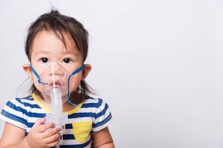 Closeup Asian face, Little baby girl sick her using steam inhaler nebulizer mask inhalation oneself on white background with copy space, health medical care Reklamní fotografie