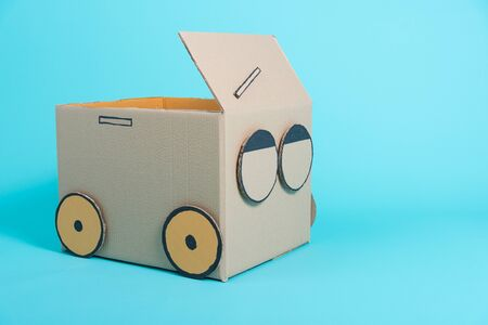 Car creative by a cardboard box imagination, summer holiday travel concept, studio shot on blue background with copy space for text