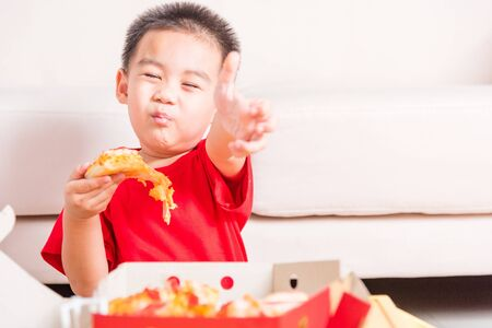 Hot Homemade, Vegetarian fast Italian food, Cute Little Child enjoying eating Delivery Pizza pepperoni, cheese many slices deliciously and show good finger thumb for like in a cardboard box at home