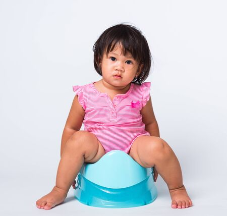 Asian little cute baby child girl education training to sitting on blue chamber pot or potty in, studio shot isolated on white background, wc toilet concept
