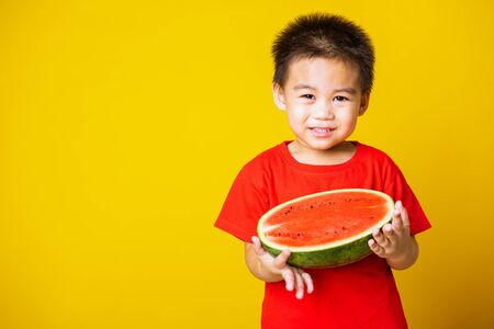 Happy portrait Asian child or kid cute little boy attractive laugh smile wearing red t-shirt playing holds cut half watermelon, studio shot isolated on yellow background