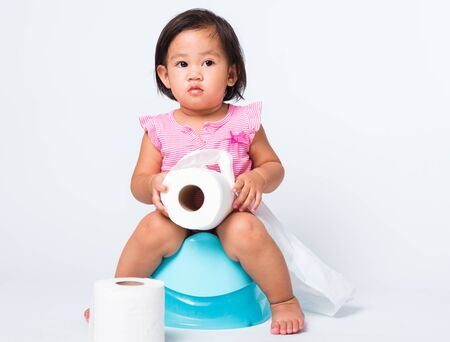 Asian little cute baby child girl education training to sitting on blue chamber pot or potty with toilet paper rolls, studio shot isolated on white background, wc toilet concept