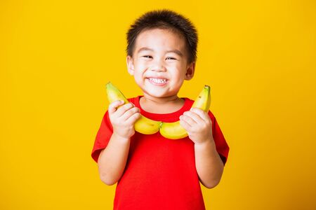 Happy portrait Asian child or kid cute little boy attractive smile wearing red t-shirt playing holds banana fruit, studio shot isolated on yellow background Standard-Bild