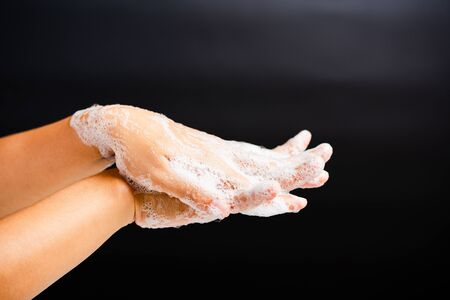 Closeup body care Asian young woman washing hands with soap have foam, hygiene prevention COVID-19 or coronavirus protection concept, isolated on black background
