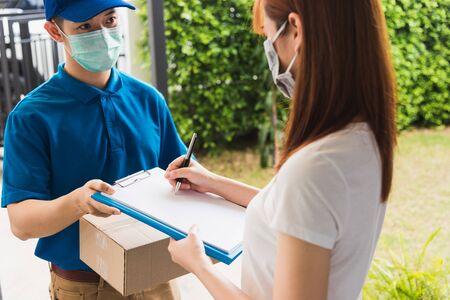Un jeune livreur asiatique fait ses courses en ligne avec une boîte aux lettres de colis dans un masque de protection uniforme coronavirus il fait une cliente de service à l'aide d'une signature au stylo sur un livre papier à la maison, COVID-19