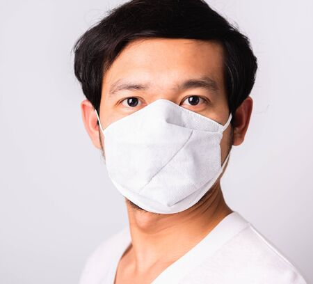 Closeup Asian handsome Man wearing surgical hygienic protective cloth face mask against coronavirus, studio shot isolated white background, COVID-19 medical concept Foto de archivo