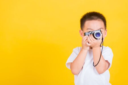 Asian Thai happy portrait cute little cheerful child boy hold photo camera compact doing taking the picture, studio shot isolated on yellow background with copy space