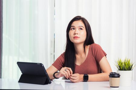 Work from home, Asian business young beautiful woman smiling sitting on desk workspace talking communicating with team video chat or conferencing on digital tablet computer at home office