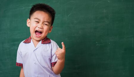 Back to School. Happy Asian funny cute little child boy from kindergarten in student uniform smiling point finger to side away space on green school blackboard, First time to school education concept